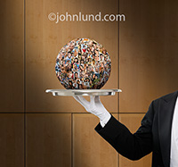 A globe of people portraits rests on a silver tray held by a butler in this photo depicting the serving up of social media in an upscale setting of a wood paneled room.