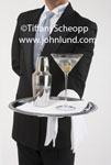 Stock image of a butler doing his job. The formally attired butler in a tux is holding a sterling sliver serving tray with a martini - up, and a sliver martini shaker. Pics of bulters working.