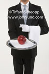 Photo of a butler standing erect with perfect posture and holding a sliver tray with an apple on it. The butler has a small white towel over his arm and is wearing a white glove on his hand. Butler in a tuxedo pic.