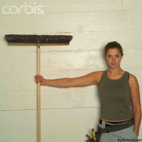 Construction woman holding a broom. In this picture the woman is wearing a tool belt, and holding onto a push broom by the handle.