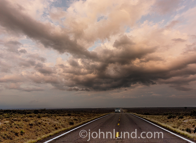 A car approaches on a long desert road under gathering storm clouds in a photo about the journey, freedom, and the way forward.