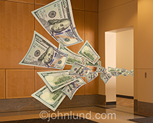 Cash flows through a corporate office in the form of one hundred dollar bills in a business stock photo about finance, working capital and money issues.