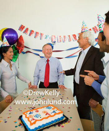 Office party shot of an older gentleman having a retirment party. Co-workers standing around a table with confetti and a cake on it. Senior retiree is wearing a red neck tie. Party decorations on the wall and folks wearing funny party hats.