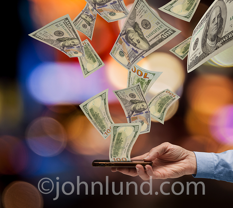 A bevy of hundred dollar bills pour forth from a mobile device in this stock photo about finance, bill paying, instant cash and access to money via smart phones.