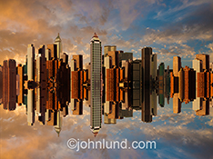 A city of tall buildings rises above its own reflection in a stock photo aimed at urban and population dense concepts.