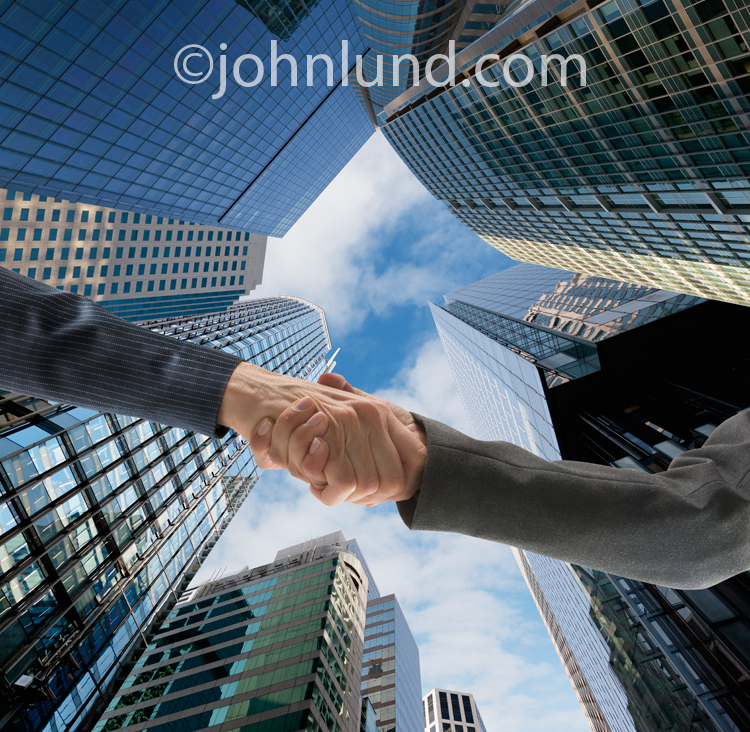 This picture of a handshake features an upwards angle with the hands surrounded by skyscraper buildings in an image about agreement and teamwork.