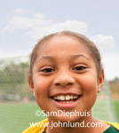 Cute adorable close up picture or portrait of a happy smiling young African american girl on the soccer field . Too cute for words.
