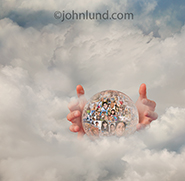 A pair of hands float around a crystal ball filled with people portraits and hovering in a sea of clouds. The image is a metaphor for social media, online social connections and the future of social media.