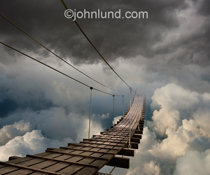 In this image a suspended foot bridge leads into a cloudscape in a metaphor for cloud computing, journeys, mystery and change. This is the way forward into the unknown.