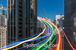 Cloud computing and networking connections are illustrated in a riveting, colorful and dynamic stock photo with lines of brilliantly colored lights streaking between tall buildings and up into the sky.