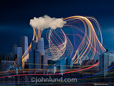 A connected city is featured in this stock photo depicting swooping and swirling colored lights streaming between an urban city and a cloud in an image about motion, energy and Internet communications.