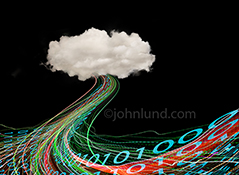 Cloud computing and data collection, management, and distribution are all vividly portrayed in this stock photo of a single cloud, on a black background, with streaming light trails and binary numbers flowing forth.