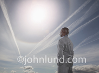 Contrails stretch over the head of a businessman looking to the sky for guidance in cloud computing issues.