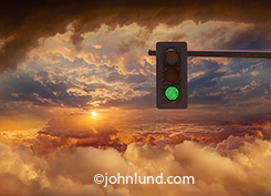 A vast blanket of clouds stretch out towards a brilliant sunset or sunrise while overhead a traffic light shines green in an image about all systems go for cloud computing, unlimited possibilities, and the sky is the limit in this concept stock photo.