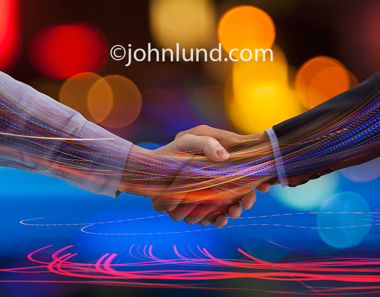 Two hands shake as colored lights stream through the hands and arms in a metaphor for communications technology, streaming data, and the way forward. This picture is rich in color and motion lending a new vibrance to an iconic symbol of agreement and succ