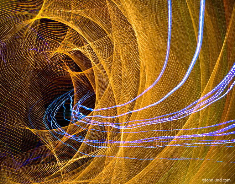 Streaks of colored light stream through a tunnel in a digital pipeline created from a intricate network of light streaks in an image about communications technology, bandwidth and networking.