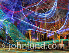 Communications technology and the resulting connections are beautifully illustrated in this photograph featuring complex wave patterns of colored light streaks engulfing a city.