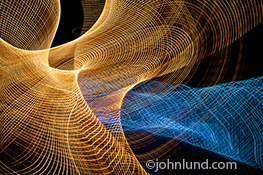 Two separate complex webs of light interesect in this image that can illustrate everything from future communications technologies to wireless communications to scientific research.