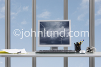 A computer monitor displays a lightning storm in an office setting in this stock photo about online change and turbulent times.