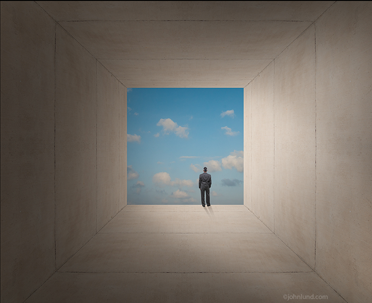 An executive stands at the edge of a cement structure gazing out at a lightly clouded sky in a futuristic and minimalist stock photo about contemplation, decisions, and leadership.