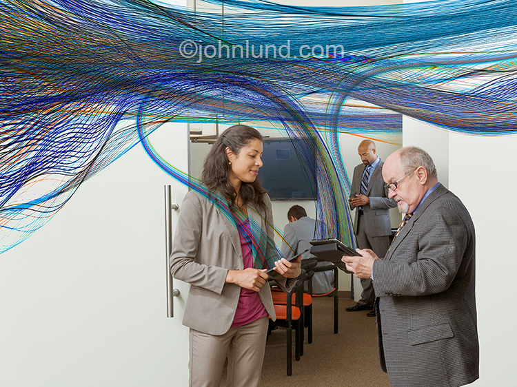 Various businesspeople are connected in an office by communications technology represented by colored lines of light, light trails, that stream across the frame of this business connection Stock photo.