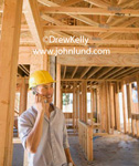 Stock photo of an Asian contractor using his cell phone at the job site. He is smiling and surrounded by open framing. Two by fours, joists, beams, and headers are all exposed. Pictues of men working for ads.