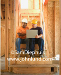 Construction worker teamwork picture.  These two construction workers are working together on a laptop because teamwork pays off.  Stock photos for business ads.