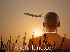 Business growth is the concept in this stock photo of a man digitally composited over a sunset, a line of construction cranes, and a commercial jet taking off.
