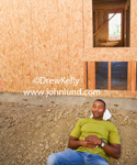Stock photo of a black male construction worker asleep on the job site. During his break this african american construction worker is resting his head on his white hard hat and laying on some rocky dirt next to the building he is helping to construct.
