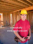 Portrait photo of a Mexican or Hispanic construction worker smiling at the camera. He is wearing a yellow hard hat and a red shirt. He is very handsome.  Hands on tool belt. Man standing in a new building under construction.  Ad pics for builders.