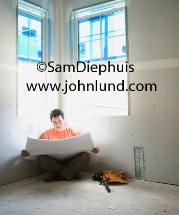 A carpenter sits in the corner of an unfinished room reading a set of blueprints with light from the two windows in the corner just above him. His toolbelt is on the floor next to him. Pictures of men working in new construction for ads.