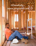 Construction worker taking a break from work. The man has short black hair, and orange T-shirt, blue jeans, and work boots.  He is sitting on the floor leaing back against the framing studs for an exterior wall. Smiling workers on break pics for ads.