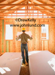 Photo of a construction worker, carpenter, or architect with his back to the camera and wearing a yellow hard hat standing in a home under construction.  The walls are not yet sheet rocked.  Construction pictures for advertising.
