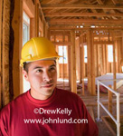 Stock photo portrait of a hispanic or latino male construction worker in a yellow hard hat inside a house or office building during the framing stage. Construction photos for ads.