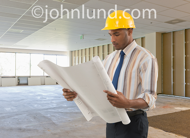 An African American male contractor in a tie and wearing a hardhat examines blueprints at an office building construction site.