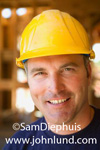 Close up portrait of a normal average looking construction worker in a yellow hard hat. Average construction worker at the job site with unfinished framing around him. A worker drills a hole in the background and out of focus. Smiling workman photos.