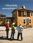 Pictures of a large construction job site. Three contractors or construction workers are standing outside in front of a large apartment bulding under construciton. Big construciton job pictures for advertisers and advertising.