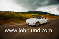 White convertible sports car driving on a rural road with dramatic dark storm clouds in the sky. Sports car pic.