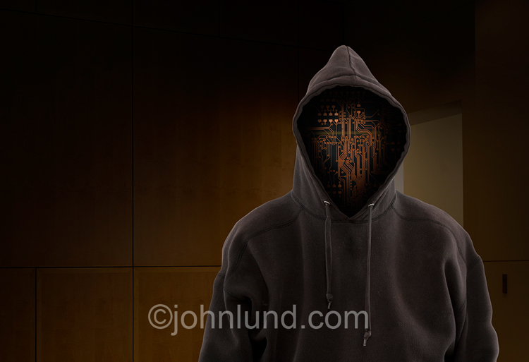 Computer circuitry serves as a face in a hoodie which is in an upscale corporate environment symbolizing corporate hacking and computer crime.