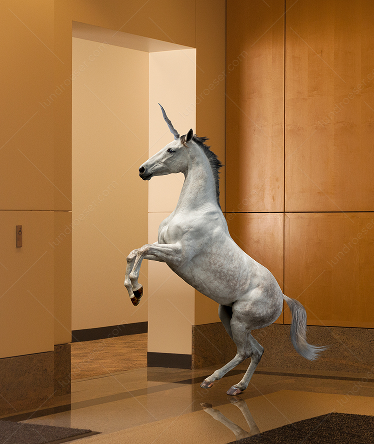 "A unicorn rears up in a corporate lobby in an image about mythical, magical and ""all powerful"" business solutions."