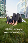 Stock photo  of a couple laying in the grass between huge office buildings.  Only the couples legs and bare feet ar visible. People laying on their backs in the grass during a break from work. Pics of people relaxing at work.