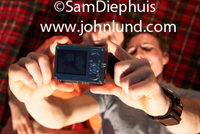 Stock image of a couple laying on a plaid blanket taking a self-portait.  The man is holding the camera up above them and they have thier heads together for the picture.