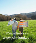 Stock photo of a young couple walking through the grass in a big green field carrying lawn chairs over their backs. Tree covered hills in the distance and a blue sky.