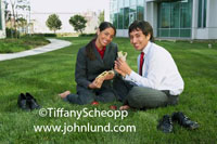 Mexican office worker couple having lunch toegther on the grass in front of their office building. The couple has removed their shoes and are barefoot.  Pics of people eating sandwiches at work outdoors. Happy smiling employees having lunch.