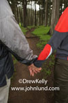 Picture of a couple holding hands as they walk on a dirt path through a dense woods or forest.  Scary looking path through the deep dark woods.  Photo of an adventure about to happen.  Walking the path together.
