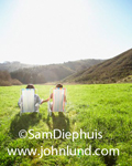 Stock photo of a young couple holding hands and sitting in lawn chairs in the middle of a green grassy medow with rolling hills in the distance under a cloudless blue sky.