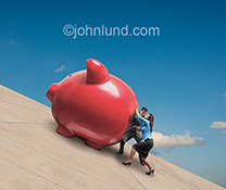A couple strain to push a giant piggy bank up a steep concrete embankment in a piggy bank stock photo about personal finance, savings, investment and retirement planning.