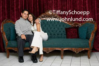 Romantic photo of a Latino couple hugging on an antique couch with a red curtain in the background.  Average looking hispanic couple on a sofa posing for a portrait. Pics of normal looking hispanic couples for advertising.