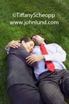 Office romance in the grass. Co-workers laying on the lawn hugging each other. Man is wearing pin striped slacks, a dress shirt, and a bright red necktie. Woman is wearing a business suit. Pics of office lovers hugging.