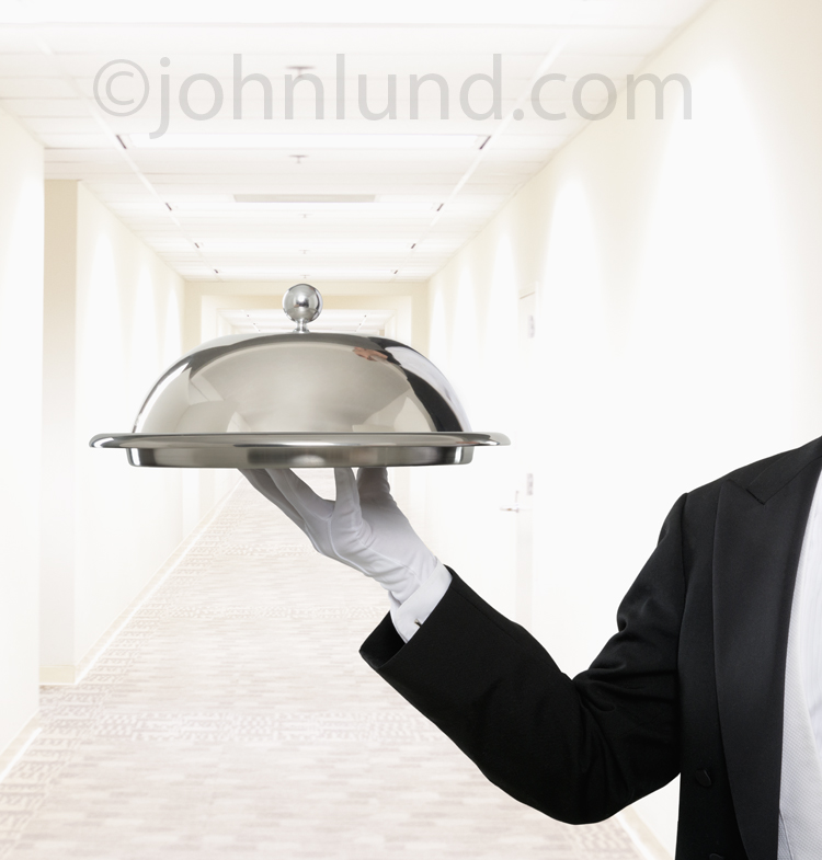 A butler, concierge or Bell Person holds up a domed silver tray in a long corridor in this picture of top shelf service and over the top luxury.